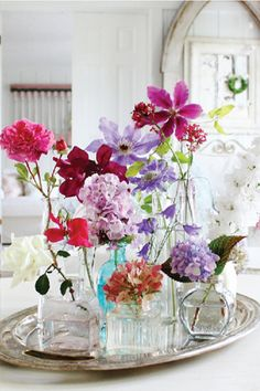so pretty....,    fresh flowers from the garden put in glass bottles and placed on silver tray makes great center piece for your table
