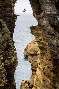 Blake Aldridge of Great Britain dives nearly 100 feet from a rock monolith during the Red Bull Cliff Diving World Series on July 20, 2012, in Islet Vila Franca do Campo in Portugal's Azores island chain. MSN On Top of The World.