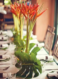 Centerpiece: fiery orange birds of paradise paired with long bamboo reeds