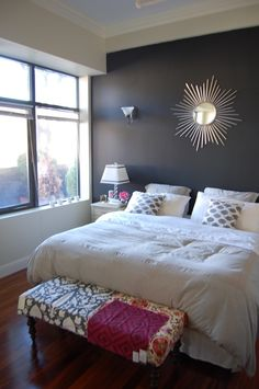 Our bedroom: king sized bed, white bedding, gray walls, dark wall behind headboard, accent color and patterns for pillows, rug, curtains, etc