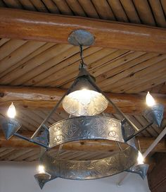 punched tin chandelier + wooden ceiling.