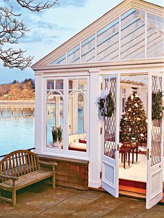This calming, glassed-in sunporch combines the nautical and the festive with potted paper whites, a Christmas tree adorned with white doves, and a simple wreath on the door.