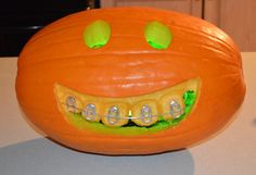 carved Halloween pumpkin with homemade braces- Pinterest inspired.  Color-changing LED light shows green in this photo.