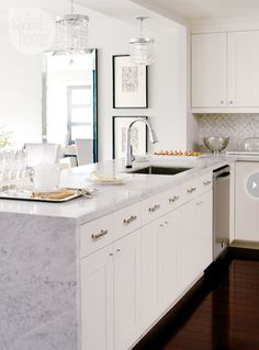 Kitchen with a marble backsplash and Carrara marble countertops. Design by Meredith Heron. Photo by Stacey Brandford. From www.styleathome.com.