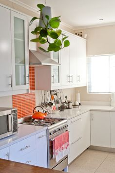 light beige kitchen white cabinets orange-red tile back splash