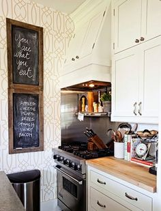 Tidy, but tight counters that have everything: utensils, scale, cookbooks, butcher block wood counter tops, potted herb, wallpaper, but don't know the pattern... a trellis of some kind?