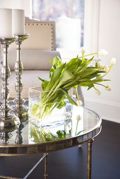 * glass, pewter candlestick, green flowers