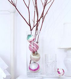 Decorate a bedside table for Christmas with a simple arrangement. Fill a tall glass hurricane with colorful ornaments and bare branches. Coordinate the ornament colors with the room's palette or stick with classic red and green.