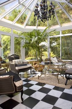 Elegant black and white tiled conservatory...love the black chandelier!