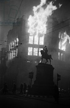 Holborn Circus ablaze after an air raid, with the statue of Prince Regent in the foreground, 16th April 1941