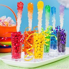 Send them over the rainbow with ombre rock candy sticks! White rock candy dipped in water & sugar sprinkles turns into a display of color! Click for this and more rainbow candy buffet ideas!