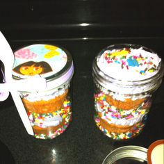 Dora cupcakes in a mason jar. Layer sprinkles, cupcake, icing, sprinkles, cupcake, icing and more sprinkles!  Perfect to-go cakes.