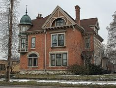 """Interesting brick and stone Queen Anne on Old Aristocracy Hill in Springfield, IL.  The stone itself is decorated.  A unique, beautifully embellished """"hanging"""" tower with hat!  The only thing these """"average"""" homes lacked were a grand porch and entrance."""