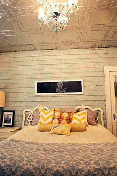 White washed wood plank walls, tin ceiling, pillows, chandelier, chalkboard