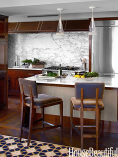 This kitchen, accented with Breccia Imperiale marble from Artistic Tile, is open to the family room.