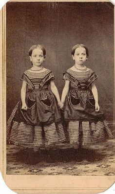 Twins girls wearing check dresses and solid color pinafores