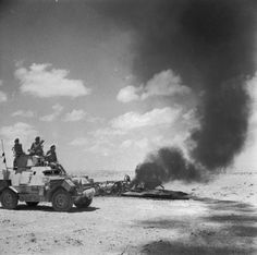 BRITISH ARMY NORTH AFRICA 1942 (E 13026)   The crew of a Marmon-Herrington armoured car investigate the burning wreckage of a German fighter, Libya, 8 June 1942.