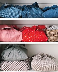 To keep bed linens organized, fold each set -- pillowcases, top and fitted sheets -- and wrap with a 1 1/2-yard square of fabric inspired by Japanese furoshiki. Then, using like colors, coordinate the sets by room or by sheet size, and shelve them together. This method makes finding the linen set you need a snap.