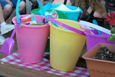 Children's inexpensive plastic sand buckets used to hold plastic tableware and napkins at outdoor picnic.
