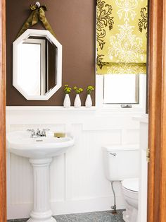 Upstairs guest bathroom: Chocolate-brown paint and ivory wainscoting visually break up the small space. And love the little details, such as the hanging mirror and window trim and Roman shade (I prefer different color combined with brown). mirror, decor, chocolate brown, color, bathrooms, white bathroom, bathroom ideas, roman shades, powder rooms