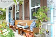 Creating curb appeal with some front porch decorating via The Space Between. #porch cottage shutters, blue houses, shutter color for gray, porch decorating, gray house wood shutters, gray house with shutters, stained wood shutters, front porches