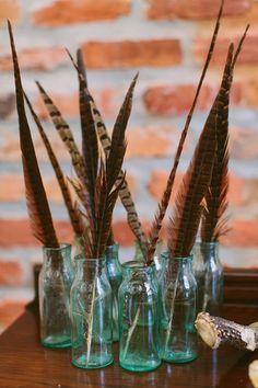 blue bottles + feather #weddingcenterpieces - photo by http://www.ashleighjayne.com - http://ruffledblog.com/green-autumn-wedding-inspiration/