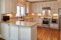 Cream cabinets, antique white cabinets, flat panel cabinets, granite counters, travertine backsplash, Kitchen Aid appliances, medium oak hardwood flooring, oil rubbed bronze faucet, under cabinet lighting, flat screen tv in kitchen,   Case Remodeling of Charlotte, Deborah Scannell Photography