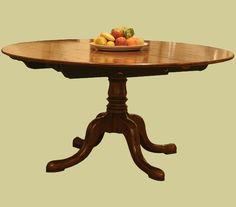 Circular extending dining table, handmade in England from solid oak and part of their bespoke reproduction dining furniture range.