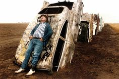 The creepiest  guy in Amarillo...Stanley Marsh III leans on one of the 10 Cadillacs buried on his ranch west of Amarillo, Texas, along Route 66, in this June 1984 photo.