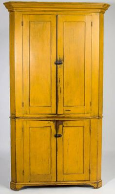 "Sold $5,500 SOMERSET CO., PENNSYLVANIA PAINTED PINE CORNER CUPBOARD, two-piece construction, well-executed molded cornice above two paneled doors in upper and lower sections divided by simple waist molding, raised on an applied cut-out bracket base. Mustard-painted surface. Circa 1830-1850. 79"" H, 41"" W, 29"" corner.Provenance: Collection of the late John and Lil Palmer, Purcellville, VA. Purchased from Dick Barnes, Old South Antiques, Brownsburg, VA, 1989."