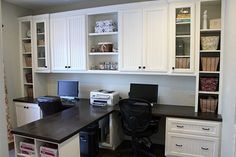 Home office with white built-in cabinets and room for two.