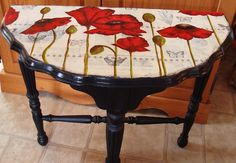 Poppies painted onto a decoupaged table top.