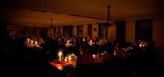 Wedding held within Greenfield Village's Eagle Tavern using candlelight and red accents.
