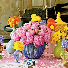 Peonies, daffodils, hyacinths, and ranunculus arranged in eclectic vases create a lush centerpiece. | southernliving.com