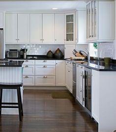 white cabinets, subway tile backsplash with black granite countertops, beadboard island, wood floors