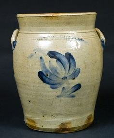 """Price Realized: $ 402.50 Cobalt-Decorated Stoneware Jar, Stamped """"MOYER. HARRISBURG,"""" circa 1858, approximately one-gallon ovoid jar with tooled shoulder, tall flaring collar and applied lug handles, decorated with a brushed cobalt tulip design. 1"""" rim chip. Glazed-over dent to one handle. Some very faint surface lines, which probably occurred in the firing and do not go through to the interior. H 9 1/2""""."""