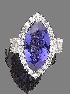 A tanzanite and diamond ring  The marquise-cut tanzanite, within a brilliant-cut diamond surround, between similarly and baguette-cut diamond shoulders, diamonds approx. 1.95cts total, maker's mark SJ