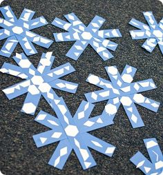 Symmetrical snowflakes made from strips of construction paper with added punched-out shapes in patterns