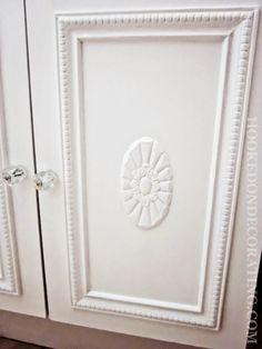 How to give a boring, outdated laminate bathroom vanity cabinet a cottage chic makeover with some molding, appliques, crystal knobs and a couple of coats of paint.