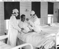 Masked medical personnel giving treatment to an influenza patient. U.S. Naval Hospital, New Orleans, Louisiana. (Circa autumn 1918)