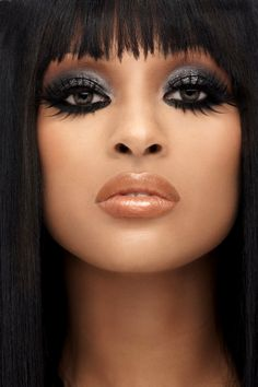Black dramatic eyeliner, silver sparkle shadow, long feathery lashes, nude bronzy lips