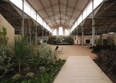 Spanish studio Langarita-Navarro Arquitectos filled a Madrid warehouse with makeshift huts and a wilderness of plants to accommodate a nomadic music academy