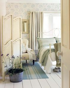 A beautiful cottage style bedroom in shades of cream, mint green, blue and lavender. Old doors as screen. Pot of flowers