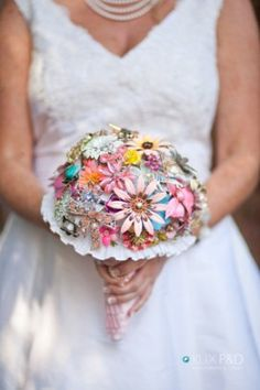 A hand crafted wedding bouquet out of vintage/antique brooches and pins collected from family members and thrift stores; also used materials from the wedding dress ...