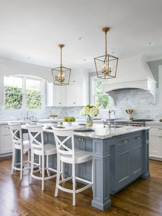 "A traditional l-shaped kitchen in San Francisco with an undermount sink, recessed-panel cabinets, grey cabinets, white splashback, marble splashback, stainless steel appliances, dark hardwood floors, an island and brown floor. Via Christine Sheldon Design. ""Once they narrowed the choices to three, Sheldon painted those colors on the cabinet surface and then had the colors tinted…"