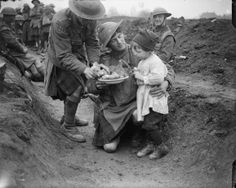 Men of the 4th Battalion, Gordon Highlanders (51st Division) feeding a French refugee child in their improvised trench near Locon, 10 April 1918.