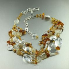 Catch the light and admiring glances with this Amber, Citrine, and Crystal Quartz necklace. Round smooth Crystal Quartz and Citrine gemstone beads are are mixed throughout with a selection of Amber and Gold Freshwater Pearls. Fine Silver beads accent the necklace with a touch of sparkling shine.