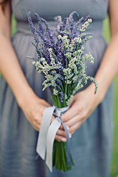 Bridesmaid wearing purple dress and holding bouquet made of lavendar with a lavendar colored ribbon - wedding photo by Meg Perotti