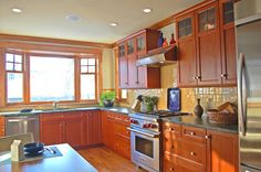 Modern Historic - The warmth of stained oak cabinets executed in an arts and crafts design coupled with improved natural and artificial lighting make this newly spacious kitchen a welcoming cozy space for the owners to enjoy for many years to come.