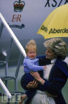Princess Diana and a young Prince Harry get a little mussed in the rain at Aberdeen's airport, September 1, 1985.